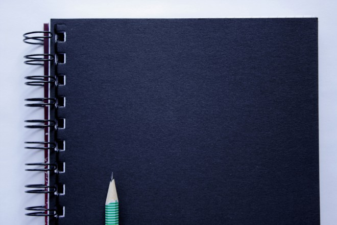 Black, last page of a notebook composed with a pencil on a bright background.