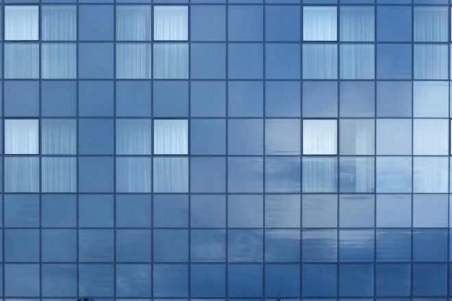 Reflection of cloudy sky in glossy wall of modern building.
