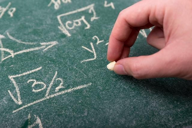 黒板にチョークで数式を書く手
